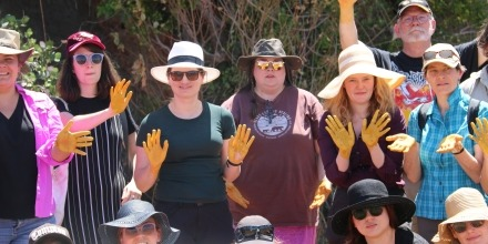 Group of students with hands painted yellow with ochre