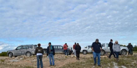 Group inspecting ground near parked vehicles
