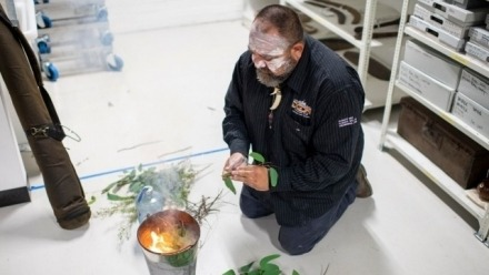 Man from Aboriginal Land Council performing smoking ceremony within museum storage